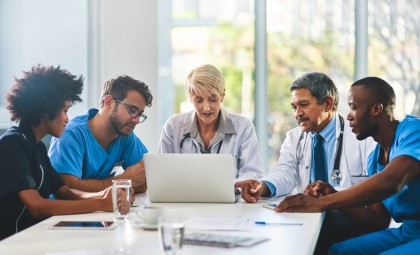Healthcare professionals gather around a laptop